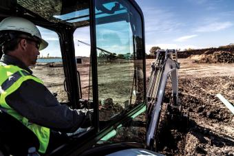 Bobcat E35 compact (mini) excavator cab with operator controlling the bucket attachment.