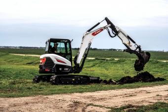 Operator Using E60 Compact Excavator With Bucket Attachment To Dig Trench Along Gravel Road