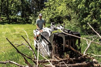 Landscaper Uses Bobcat MT100 Mini Track Loader With Grapple Attachment To Move Large Tree Branches