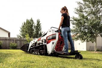 Landscaper Using Bobcat MT55 Mini Track Loader With Ride On Platform To Complete Work In Yard