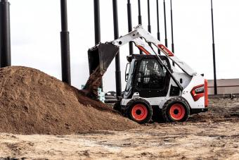 Operator Using Bobcat S510 Skid-Steer Loader With Bucket Attachment To Dump Dirt Onto Pile