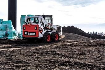 Operator Using Bobcat S590 Skid-Steer Loader With Pallet Fork Attachment To Move Barrels