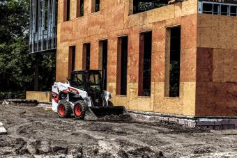 Construction Worker Using Bobcat S62 Skid-Steer Loader With Bucket Attachment To Move Dirt On Jobsite