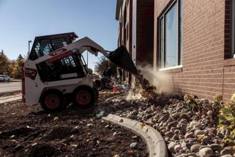 Operator Using Bobcat S70 Skid-Steer Loader With Bucket Attachment To Dump Stones Into Bed Of Rocks Lining Building Wall