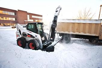 Snowblower attachment mounted on a S630 skid-steer loader removes snow from a walkway on a college campus.