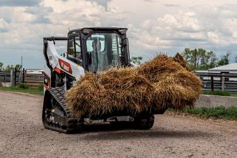 Farmer Using Bobcat T66 Compact Track Loader With Industrial Grapple Attachment To Move Hay On Operation